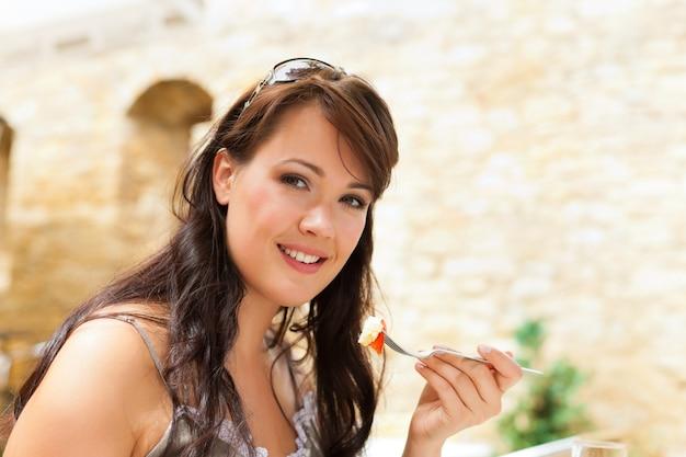 Женщина ест перед кирпичной стеной замка