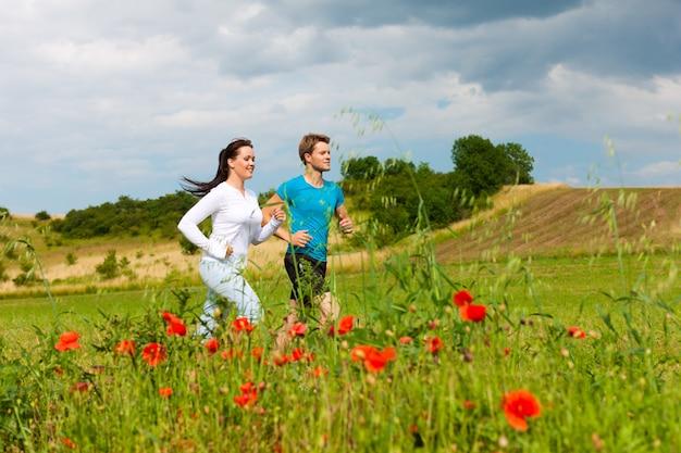 若い陽気なカップルは外でジョギングします。