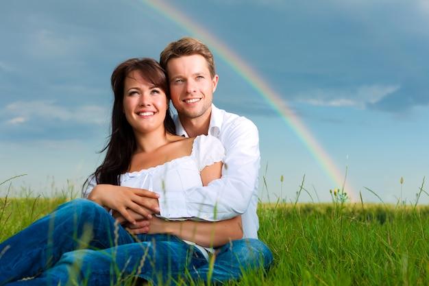 Женщина и мужчина сидят на лугу под радугой