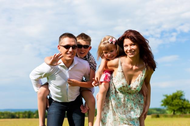 幸せなお母さんとお父さんが子供のおんぶを運ぶ