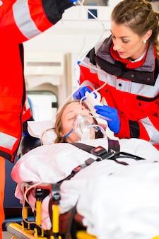 担架で負傷した女性を助ける救急車