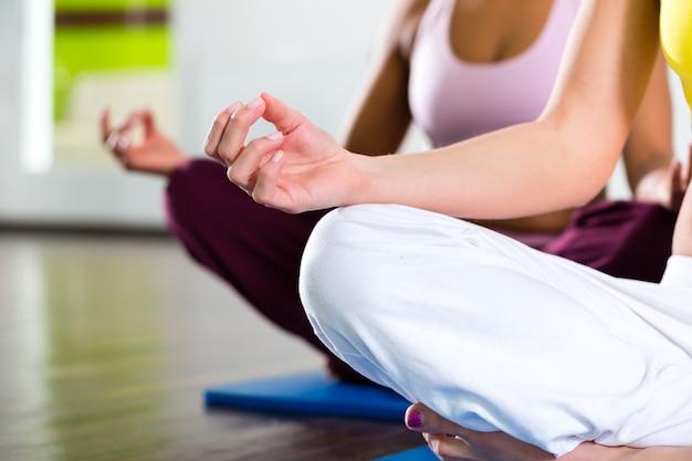 Женщины в спортзале делают упражнения йоги для фитнеса