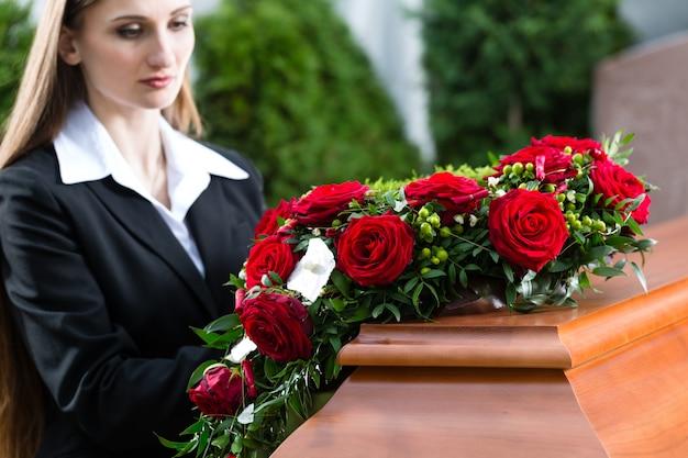 Траурная женщина на похоронах с гробом