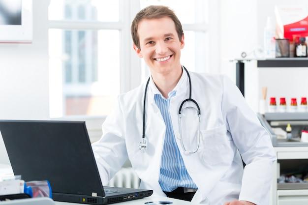 ラップトップ上のクリニックで若い医者の肖像画