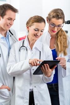 タブレットコンピューターのクリニックで若い医師のチーム