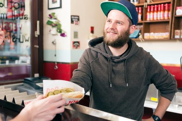 Человек с хот-догом в закусочной быстрого питания