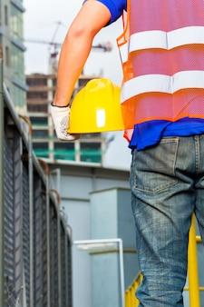 Рабочий на стройке в шлеме или каске