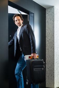 ホテルの部屋に入る荷物を持つ若いゲスト