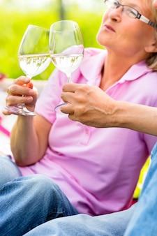 ワインを飲んでピクニックを持つ幸せな先輩