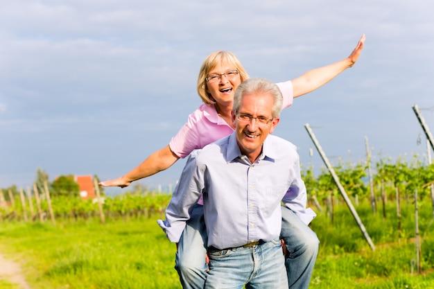 年配の男性と女性が手をつないで歩く