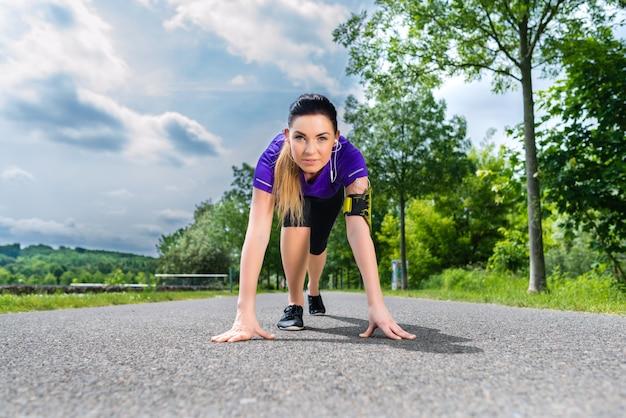 Спорт на открытом воздухе - молодая женщина делает фитнес в парке