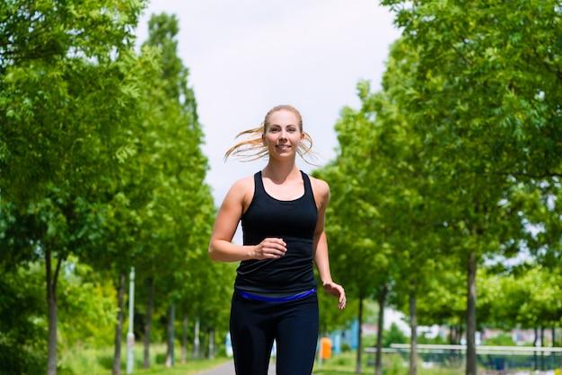 Спорт на открытом воздухе - молодая женщина работает в парке