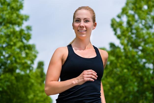 屋外スポーツ-公園で走っている若い女性