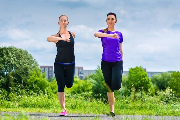 Спорт на открытом воздухе - молодые женщины занимаются фитнесом в парке