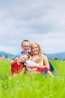 屋外の芝生の上に座って幸せな家族