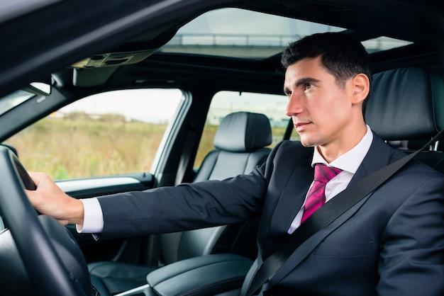 Человек за рулем в своей машине в деловой костюм