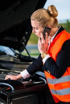 修理サービスを呼び出す車のエンジンの問題を持つ女性