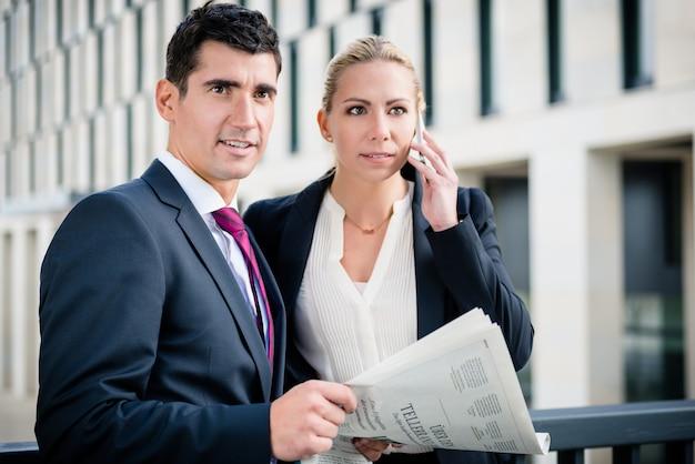 ビジネスの男性と女性の紙と電話