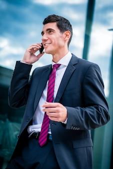 電話で話しているスマートな服を着た男