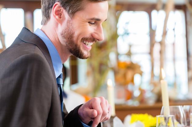 Мужчина на бизнес-ланче проверяет почту на телефоне