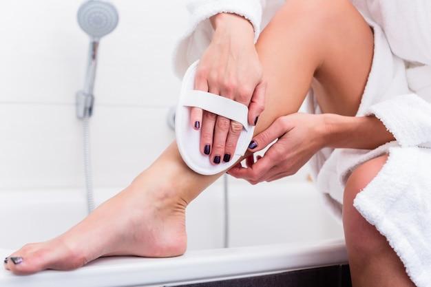 彼女の足で剥離を適用する女性