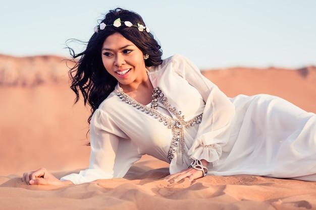 Женщина лежит в песке аравийской пустыни