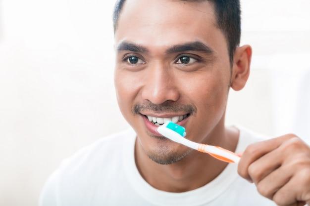 Азиатский мужчина чистит зубы