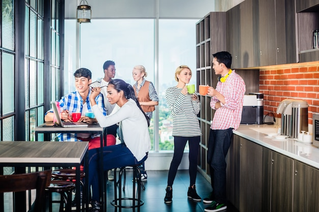 新興企業のラウンジでコーヒーを飲んでいるチーム