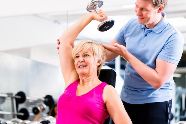 Старшая женщина на тренировке спорта в спортзале с тренером