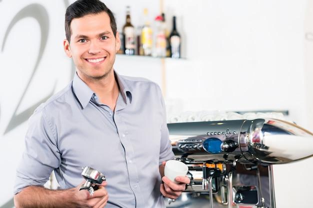 若い男が現代の自動コーヒーマシンに近いポーズ