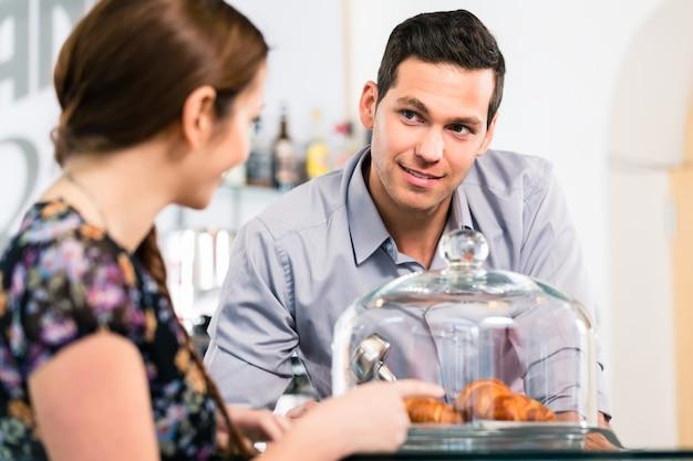 Дружелюбный официант предлагает молодой женщине-клиенту свежий французский к