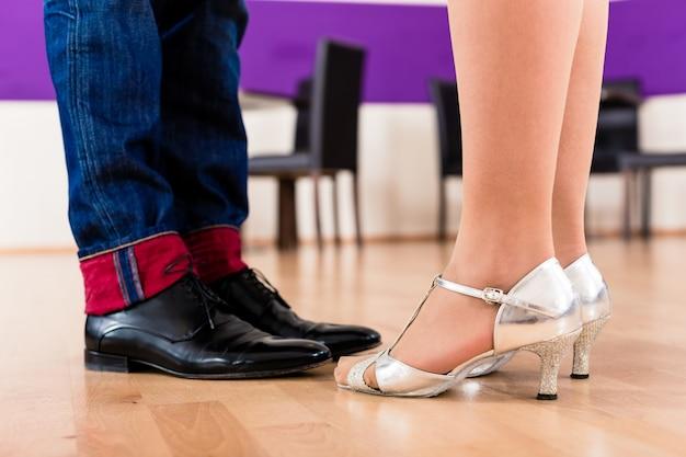 女性と彼女のダンスシューズを持つ男