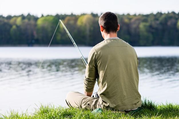 彼のロッドで湖釣りで草の中に座っている釣り人