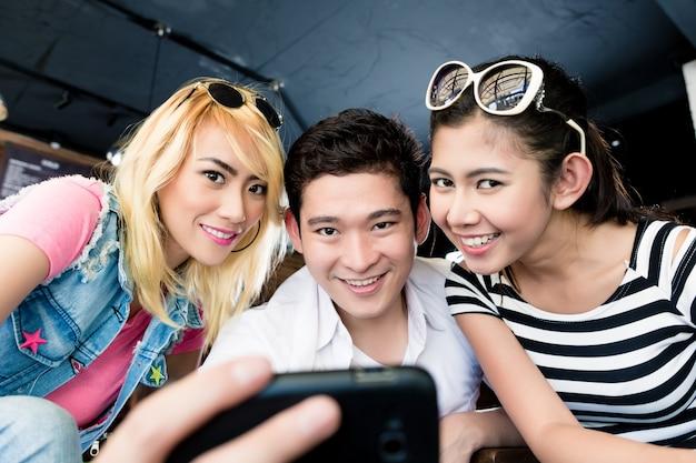Группа азиатских женщин и мужчина делает селфи с телефоном