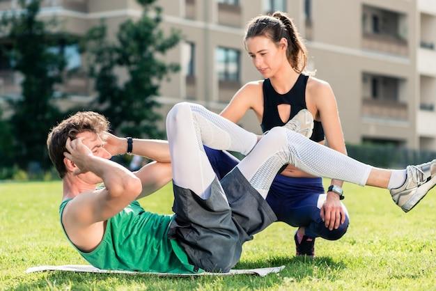 Человек делает хрустит с тренером по фитнесу