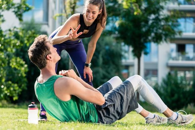 Женский фитнес-тренер мотивирует человека, делая хрустит