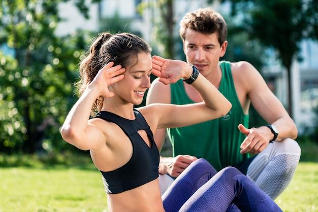 Женщина делает хрустит со своим тренером по фитнесу