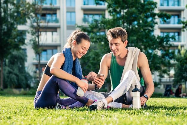 Молодая пара после тренировки с помощью мобильного телефона