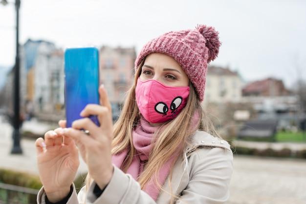 Женщина, носящая коронную маску, делающая селфи с телефоном