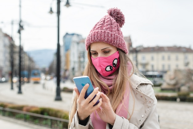 Тревожная женщина в маске короны проверяет новости по телефону