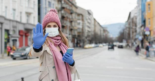 一時停止の標識を与える空のロックダウン都市の女性