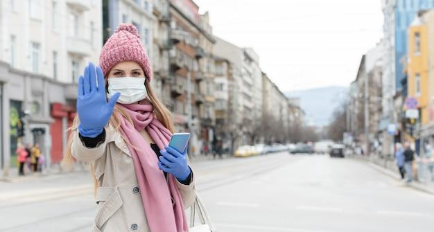 カメラに向かって一時停止の標識を与えるコロナマスクを着ている女性
