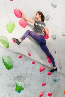 若い女性の人工岩を登る