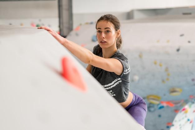 クライミングウォールに登る女性