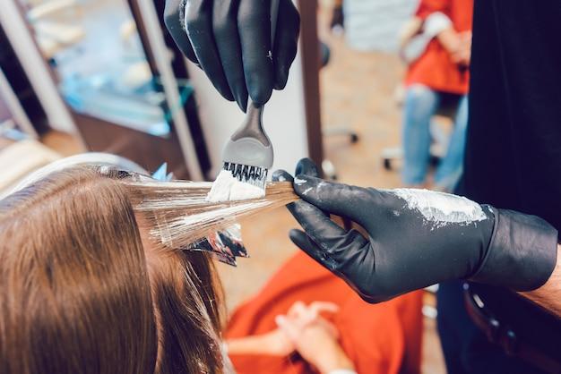 女性の髪を着色する美容師