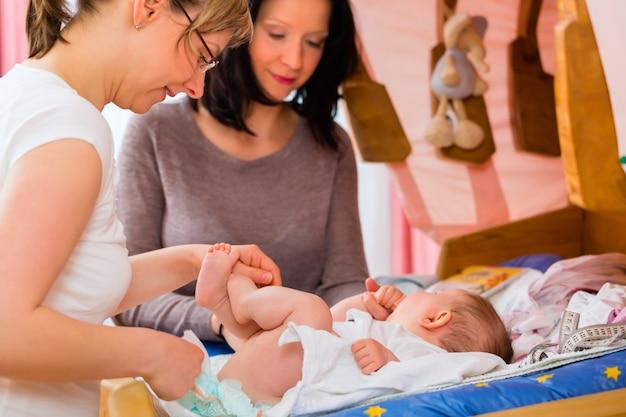 生まれたばかりの赤ちゃんを調べる助産師