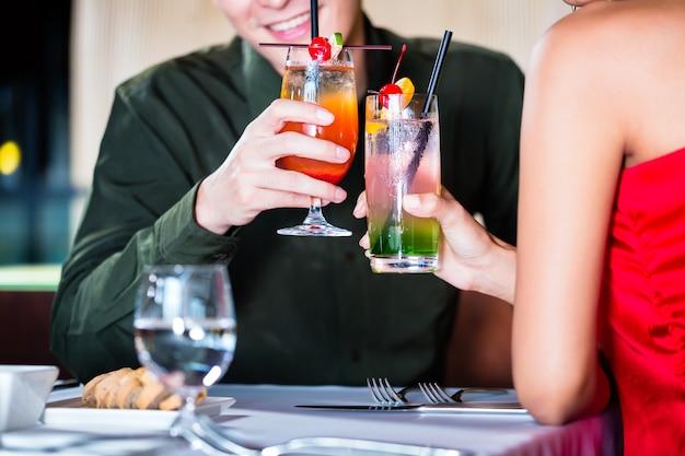 アジアのカップルが派手なバーでカクテルを飲む