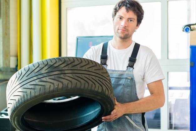 自動車整備士が車のワークショップでタイヤを交換