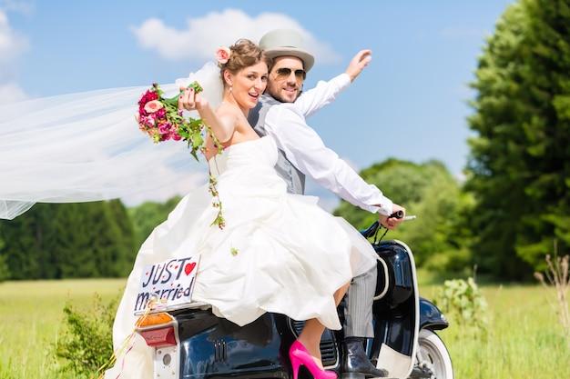 Свадебная пара на мотороллере только что вышла замуж