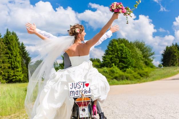 モータースクーターの結婚式のカップルはちょうど結婚した